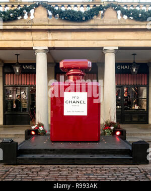 A giant replica of a red, Christmas-styled Chanel No 5 perfume outside the Chanel shop in Covent Garden in central London, England, UK. - Stock Image