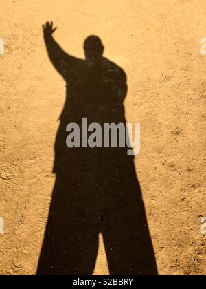A shadow of a man waving. - Stock Image
