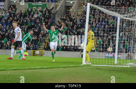 National Football Stadium at Windsor Park, Belfast, Northern Ireland. 21 March 2019. UEFA EURO 2020 Qualifier- Northern Ireland v Estonia. Action from tonight's game. George Saville (6) and Kyle Lafferty plus fans celebrate as Niall McGinn's shot put them into the lead on 55 mins. Credit: David Hunter/Alamy Live News. - Stock Image