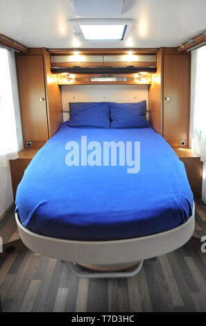 Double bed in rear part of a camper - Stock Image