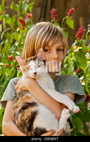 Portrait of boy holding cat , outside.With MR. - Stock Image