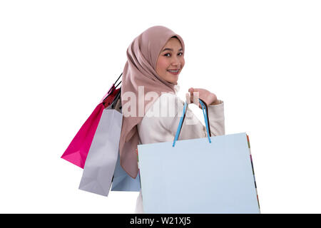 woman pregnant standing looking back carrying shopping bags at white background - Stock Image