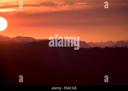 Blazing sunset sky over mountains, with sun's orb - Stock Image