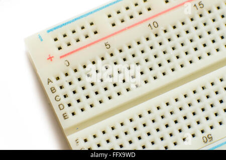 Corner of a solderless electronics prototyping board (breadboard) on a white background. - Stock Image