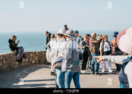 Portugal, Sintra, June 26, 2018: People or tourists, including groups of Asian women, on Cape Roca. In the background is the Atlantic Ocean. - Stock Image