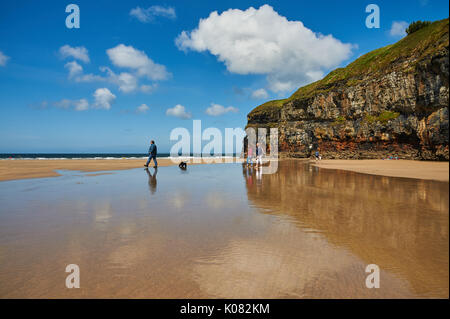 Low tide on Ballybunion beach, County Kerry with the sky and people reflected in a pool of water on a summer's day. - Stock Image