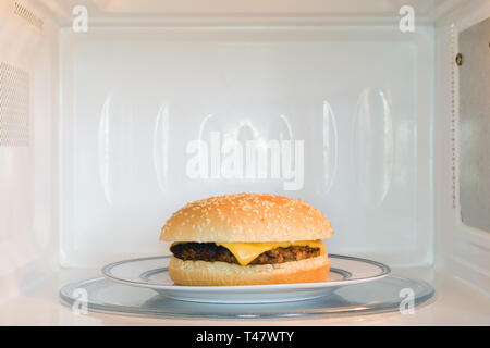 Unappealing microwavable cheese burger on a plate in a microwave oven - Stock Image