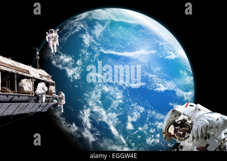 A team of astronauts perform work on a space station while orbiting above an alien water covered planet. Clouds - Stock Image