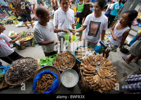 A tuyo, or dried fish, vendor conducts business at a market in Roxas, Oriental Mindoro, Philippines. - Stock Image