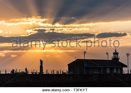 Morecambe, Lancashire, UK, 9 April 2019. UK Weather: A beautiful sunset over the Stone Jetty and Morecambe Bay as the clouds split the sunlight into distinct rays fanning out above the Mythical Bird Sculpture and the old station building. The spectacular sunsets at Morecambe and the view of the Lake District Hills across the bay continue to attract tourists throughout the year. Credit: Keith Douglas News/Alamy Live News - Stock Image