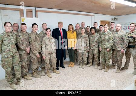 U.S. President Donald Trump and First Lady Melania Trump pose with U.S. service members during a surprise visit to Al Asad Air Base December 26, 2018 in Al Anbar, Iraq. The president and the first lady spent about three hours on Boxing Day at Al Asad, located in western Iraq, their first trip to visit troops overseas since taking office. - Stock Image