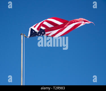 An American flag unhooked from the line twisting in the wind against a clear blue sky. - Stock Image