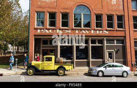 ASHEVILLE, NC, USA-10/17/18: Three people walk past Pack's Tavern on Spruce Street, with vintage Pack's Tavern pickup setting in front. - Stock Image