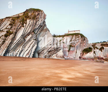 Flysch cliffs in the geological park at Itzurun Beach, with the Chapel of San Telmo on the cliff top, Zumaia, Basque Country, Spain. - Stock Image