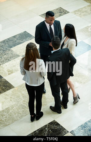 Business people discussing in hotel lobby - Stock Image