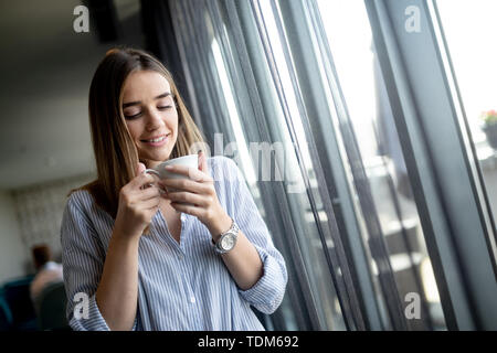 Beautiful business woman having coffee break at the office . - Stock Image