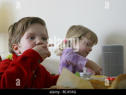 Two caucasian young self-dependant children eating lunch with hands at dining table indoors - Stock Image