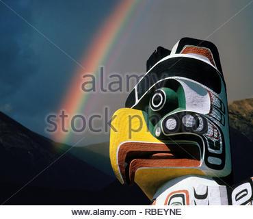 Totem Pole and rainbow British Columbia Canada. - Stock Image