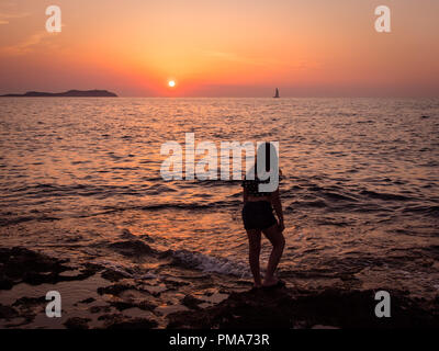 A young girl watches the sunset over San Antonio bay, Ibiza - Stock Image