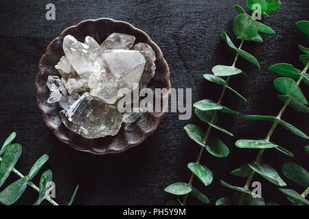 Eucalyptus and Smoky Quartz Crystals on Black Table - Stock Image