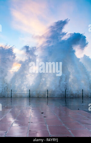 Waves from storm Diana crashing up in the air on the seafront at Penzance with a colourful sunrise behind - Stock Image