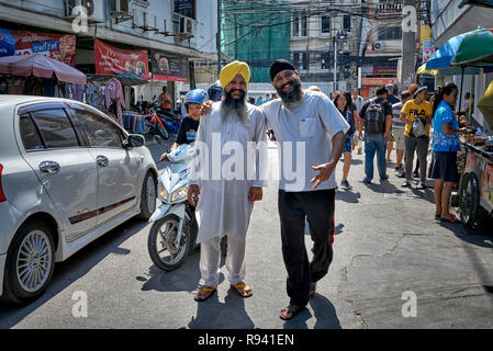 Indian Sikh man in traditional Kurta pajama shirt and turban headwear against his western attired counterpart - modern versus traditional - Stock Image