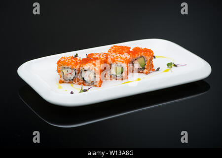 sushi in a plate on a black background with reflection. fish roll - Stock Image