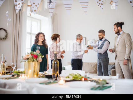 A man pouring guests wine on a indoor family birthday party. - Stock Image