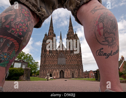 Unusual view of west front of Lichfield Cathedral seen through man's tattooed legs which read Forever England - Stock Image
