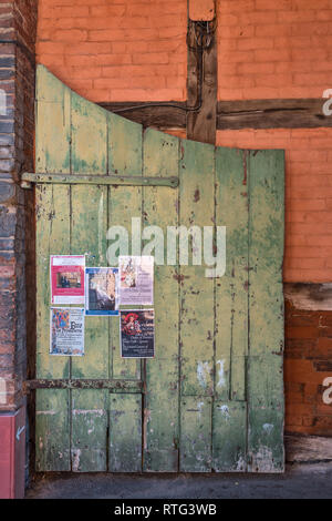 Leominster, Herefordshire, UK. An old green gate against an ochre coloured wall in a back street of this quiet English country town - Stock Image