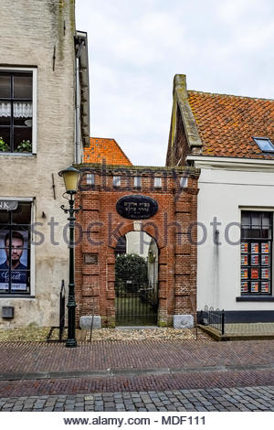 Brick doorway to private courtyard in Elburg, Netherlands with inscription (Psalm 55 Verse 15) that reads 'Let death take my enemies by surprise.' - Stock Image