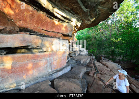 Female tourist looking at the rock art at Ubirr, Kakadu National Park, Northern Territory, Top End, Australia - Stock Image