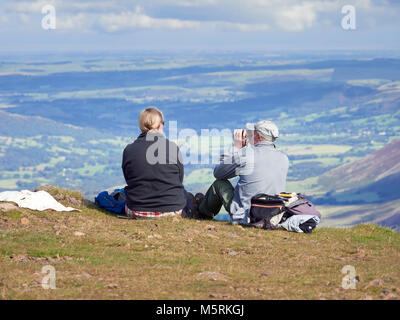 LAKE DISTRICT, CUMBRIA, ENGLAND, UK - SEPTEMBER 02, 2017: A male and female hiker sat down resting on the summit - Stock Image