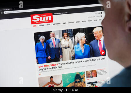 Man sitting at a computer monitor browsing through the Internet looking at The Sun newspaper website on the World Wide Web using an Internet Browser. - Stock Image