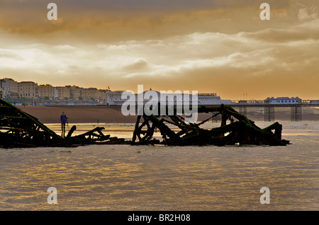 Silhouetted remnants of the West Pier with The Palace Pier beyond Brighton. East Sussex, England - Stock Image