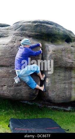 rock climber bouldering at Burbage Edge South, Derbyshire, Peak District National Park, England, UK, United, Kingdom - Stock Image