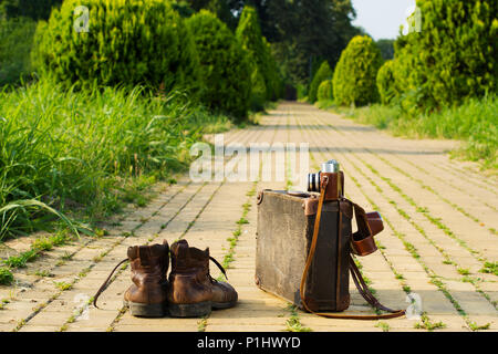 Traveling light! Shabby ankle boots next to a vintage cardboard suitcase, a film camera in its open leather case, and a yellow brick road. - Stock Image