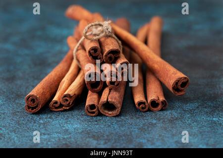 Cinnamon sticks on blue background. Dark - Stock Image