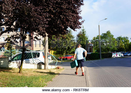Poznan, Poland - July 10, 2018: Man with tools walking on a sidewalk at the Stare Zegrze district - Stock Image
