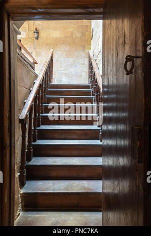 Open wooden door revealing wooden old staircase going up with with reflections of the stairs on the door located at the House of Egyptian Architecture - Stock Image