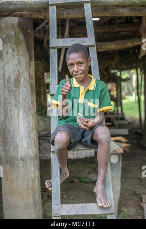 A boy sitting on a ladder to his stilt house, Swagup Village, Upper Sepik, Papua New Guinea - Stock Image