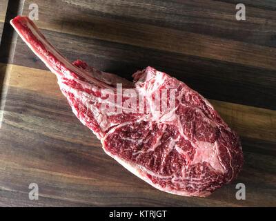 Close up of raw beef meat. Tomahawk ribeye steak, bone-in, on wooden cutting board. - Stock Image