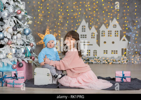Two girls in a Christmas decorated studio in pastel colors. - Stock Image