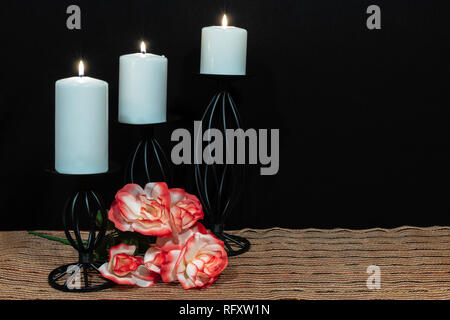 Beautiful orange and white roses, white candle perched on black candle holders on mesh place mat and wooden table with dark background. Valentines, Mo - Stock Image