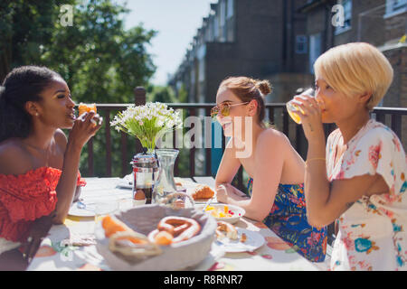 Young women friends enjoying brunch on sunny apartment balcony - Stock Image