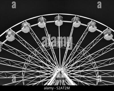 A bright white Ferris wheel with pods to ride in. Great fun even though you just go round in circles! Photo Credit - © COLIN HOSKINS. - Stock Image