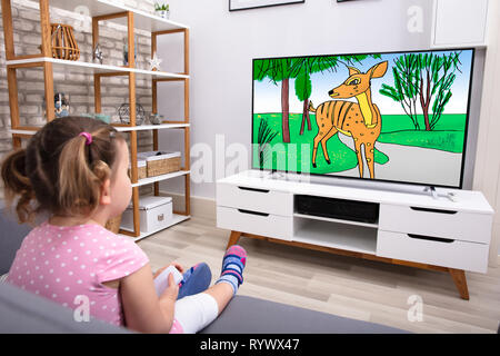 Rear View Of Innocent Girl Sitting On Sofa Watching Cartoon On Television - Stock Image