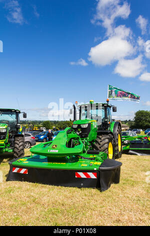 John Deere tractor with front-mounted F310R mower conditioner attachment  on the Tom Dirom agricultural contractor trade stall at the Arthington show. - Stock Image