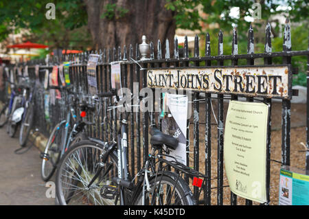 random bicycles are locked to the iron railings in Cambridge city centre by Saint Johns Street - Stock Image