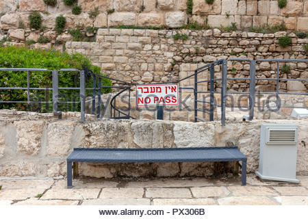 Barrier with a 'No Pass' Warning Sign written in English and Hebrew; Blocking a spiral staircase in the Old City of Jerusalem, Israel - Stock Image